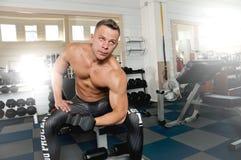 I forti uomini atletici che pompano su muscles e treno nell'allenamento della palestra Fotografia Stock