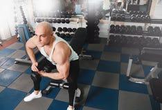 I forti uomini atletici che pompano su muscles e treno nell'allenamento della palestra Immagine Stock