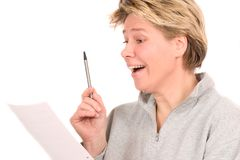I found the solution. Blond mature woman looking at a document and looking as if she found the golden egg Royalty Free Stock Photography