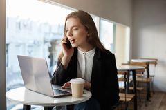 I Found Your Number Online And Want To Make Reservation. Indoor Shot Of Busy Attractive Woman In Cafe, Looking At Screen Stock Photography