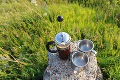 I francesi premono con caffè e due tazze del metallo su un supporto di pietra fra la pianta dell'estate all'aperto Immagini Stock