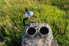 I francesi premono con caffè e due tazze del metallo su un supporto di pietra fra la pianta dell'estate all'aperto Fotografia Stock Libera da Diritti
