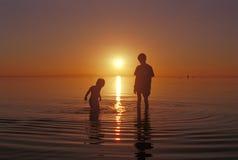 I fratelli che giocano nell'acqua al Gran Lago Salato tirano Immagini Stock Libere da Diritti