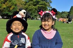 I fratelli germani con il grandi cappello di Mickey e capelli di Minnie legano Immagini Stock