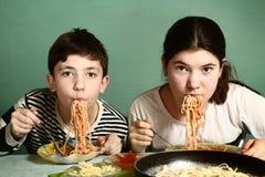 I fratelli germani teenager felici ragazzo e ragazza mangiano gli spaghetti Immagini Stock