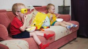 I fratelli si siedono sul sofà a casa e guardano la TV Mangi i bastoni ed il sorriso del cereale stock footage