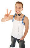 I am free to listen my music. Smiling handsome young man in casual style with headphones shows sign victory, isolated on white background stock photos