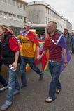 I frequentatori di festival tengono le mani e la bandiera del Rainbow Immagini Stock