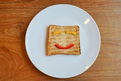 I fronti sorridenti dipinti sul pane della fetta, concetto felice della prima colazione fotografie stock