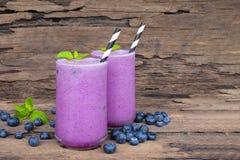 I frullati del mirtillo ed il mirtillo del yogurt fruttificano per il dimagramento su un fondo di legno fotografie stock libere da diritti