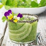 I frullati freschi dal cetriolo, dalla menta e dal miele in un vetro sono decorati con i fiori commestibili di una viola del giar Fotografia Stock