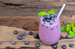 I frullati succo del mirtillo e la bevanda del nero della frutta del mirtillo deliziosa in una mattina di vetro bevono da un fond fotografia stock