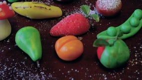 I frutti del marzapane sono disposti su un bordo marrone di legno su una tavola stock footage