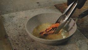 I frutti di mare che cucinano il cuoco unico di ricetta girano le tenaglie del gamberetto stock footage