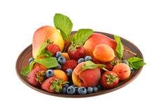 I frutti e le bacche si mescolano in piatto ceramico isolato su bianco Fotografia Stock