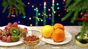 I frutti ed i dadi con miele sono sulla tavola con una palla decorata dell'albero di Natale e le luci sono bokeh confuso nel back stock footage