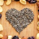 I frutti misti, i dadi ed il cuore del seme di chia sul tagliere di legno del grano, hanno sistemato nel quadrato per i media, le Fotografie Stock Libere da Diritti