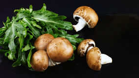I funghi crudi freschi bruniscono i funghi prataioli e la rucola verde su un dar Immagini Stock