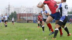 I funzionamenti del giocatore di rugby con una palla e le protezioni provano a fermarlo prima di una linea stock footage