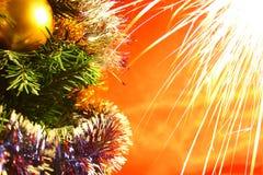 I fuochi d'artificio di festa si avvicinano alle decorazioni di natale sull'albero con fondo rosso Fotografia Stock