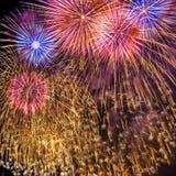 I fuochi d'artificio visualizzano sul fondo scuro del cielo Fotografie Stock