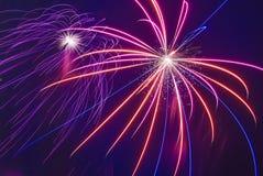 I fuochi d'artificio visualizzano sul fondo scuro del cielo Immagini Stock