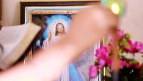 I fuochi spostano Jesus Photos per esaminare in controluce, mano di A con un fiammifero che accende una candela nella tavola video d archivio