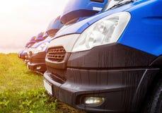 I furgoni blu del carico stanno in una fila, un trasporto su autocarro e una logistica, un'industria di autotrasporti e un sole immagine stock libera da diritti
