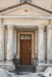 I gården som är främst av huset, är majestätiska kolonner och den gamla cykeln nära Arkivbild