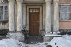 I gården som är främst av huset, är majestätiska kolonner och den gamla cykeln nära Royaltyfria Bilder