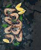 I gamberetti crudi freschi con il limone, le erbe e le spezie sullo scheggiato su ghiacciano il contesto scuro della pietra dell' fotografie stock libere da diritti
