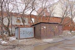 I garage arrugginiti del metallo sono macchiati con le iscrizioni illeggibili sui precedenti di un muro di mattoni rosso distrutt Immagini Stock