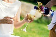 I gata är champagnen hällda exponeringsglas royaltyfri bild
