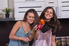 I gemelli felici si chiudono sul ritratto nella cucina su fondo Immagini Stock