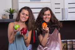 I gemelli felici si chiudono sul ritratto nella cucina su fondo Immagine Stock