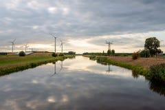 I generatori eolici ed i piloni di alta tensione hanno riflesso nell'acqua immagini stock