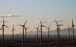 I generatori eolici si siedono su una montagna distante all'alba Fotografia Stock