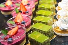 I generi differenti di dessert dolce agglutina con le bacche e il te verde Fotografia Stock
