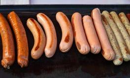 I generi differenti di salsiccie sono fritti sulla stufa Immagine Stock