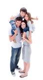 I genitori allegri che danno i loro bambini trasportano sulle spalle il giro Fotografia Stock Libera da Diritti