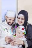 I genitori arabi sorridenti insegnano al per la matematica sullo smartphone Fotografia Stock Libera da Diritti