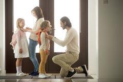 I genitori che aiutano la preparazione dei bambini vanno a scuola la condizione al corridoio fotografia stock libera da diritti