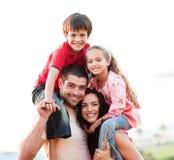 I genitori che danno i bambini trasportano sulle spalle i giri Immagini Stock Libere da Diritti