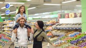 I genitori comprano i dolci al deposito, la figlia si siede sulle spalle di suo padre archivi video
