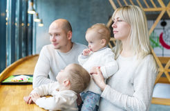 I genitori con due piccoli bambini guardano dalla finestra Fine settimana della famiglia in caffè della città fotografie stock libere da diritti