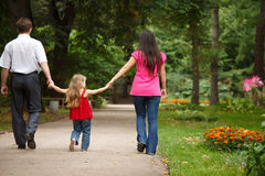 I genitori con la figlia camminano sul giardino di estate Fotografie Stock Libere da Diritti