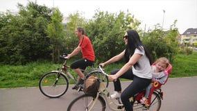 I genitori con i loro bambini stanno guidando sulle bici Tempo spendente della famiglia felice insieme archivi video