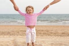 I genitori della famiglia sono mani del bambino della holding sulla spiaggia Fotografie Stock Libere da Diritti