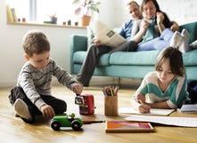 I genitori di amore della famiglia sorvegliano i piccoli bambini fotografia stock