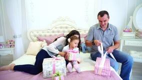 I genitori e la figlia adorabili nelle difficoltà festive dell'umore e preparano i regali per i parenti che si siedono sul letto  stock footage